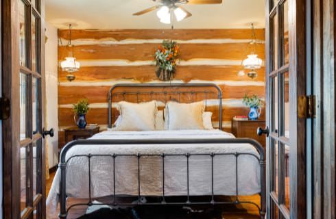 Bed with metal frame and white bedding with wood log paneling on the wall behind