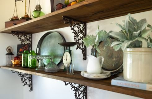 Close up view of wooden shelving with trinkets, plants, jars, bottles, and other antiques